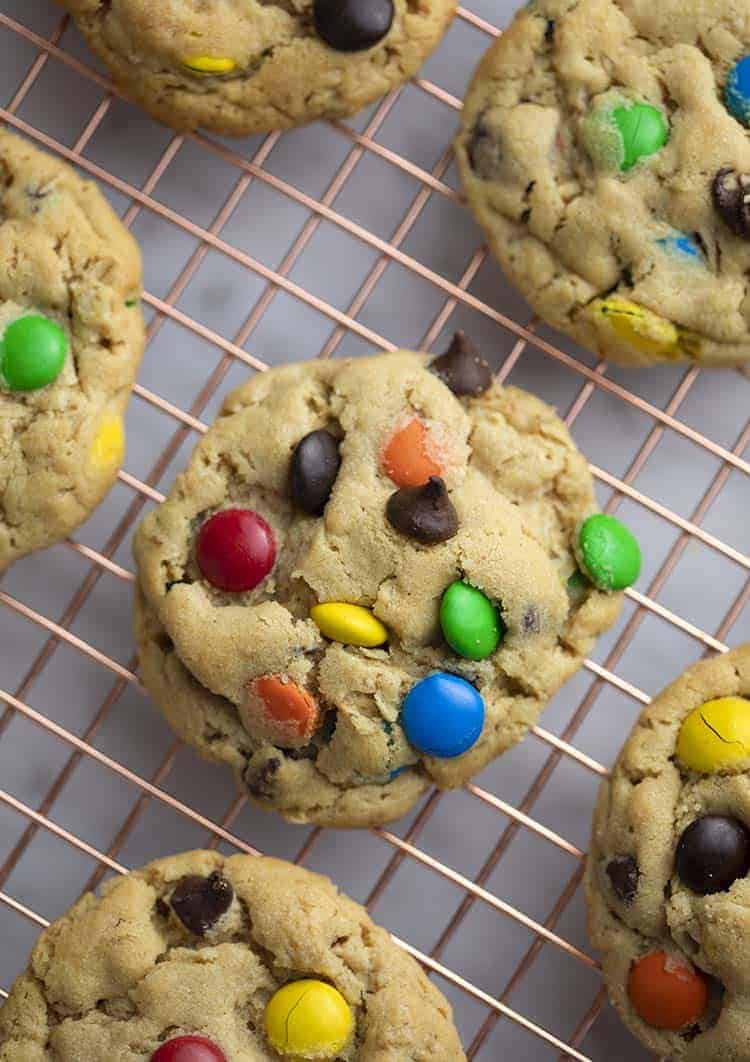 a close up top down photo of a monster cookie on a cooling rack.