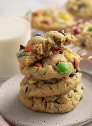 Monster cookies stacked on a grey plate next to a glass of milk.