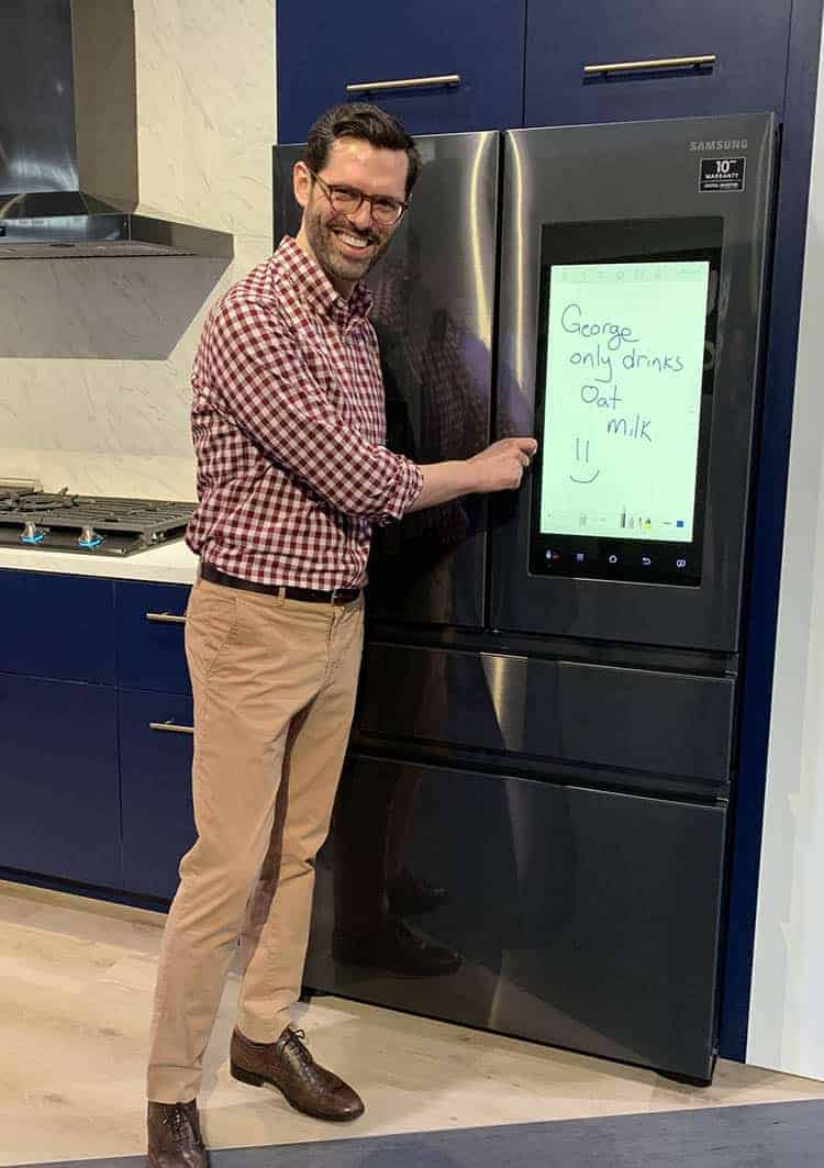 John standing next to a refrigerator