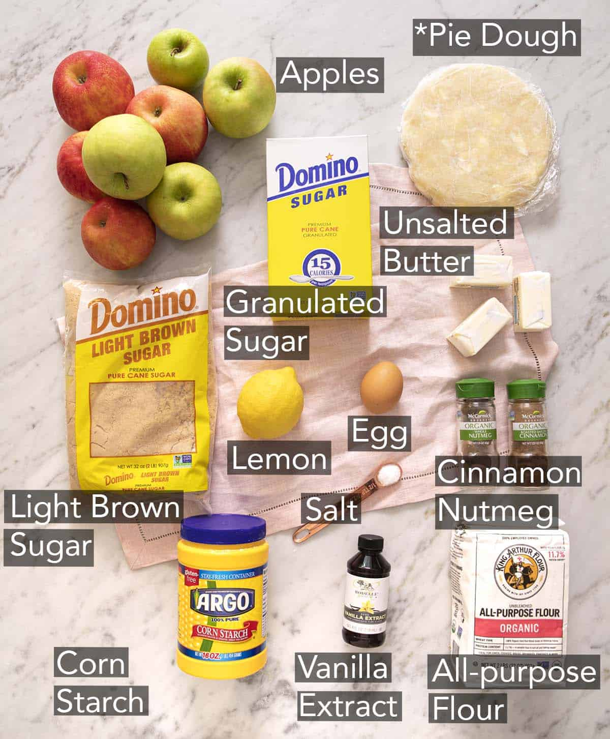 Ingredients to make apple crumble pie on a marble counter.