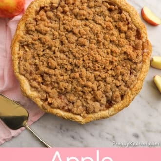 An apple crumble pie on a marble counter.