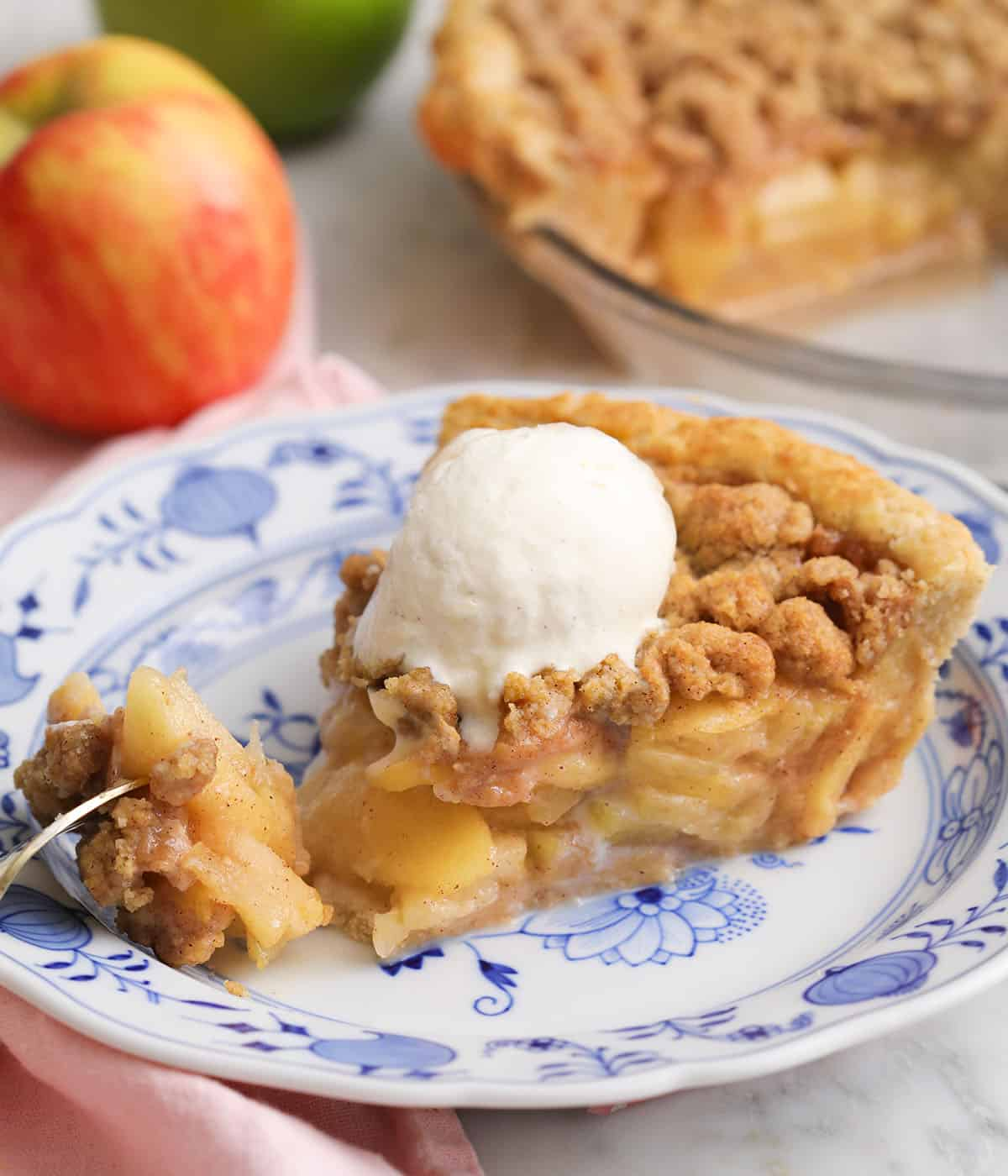 Ice cream melting into a piece of warm apple crumble pie.