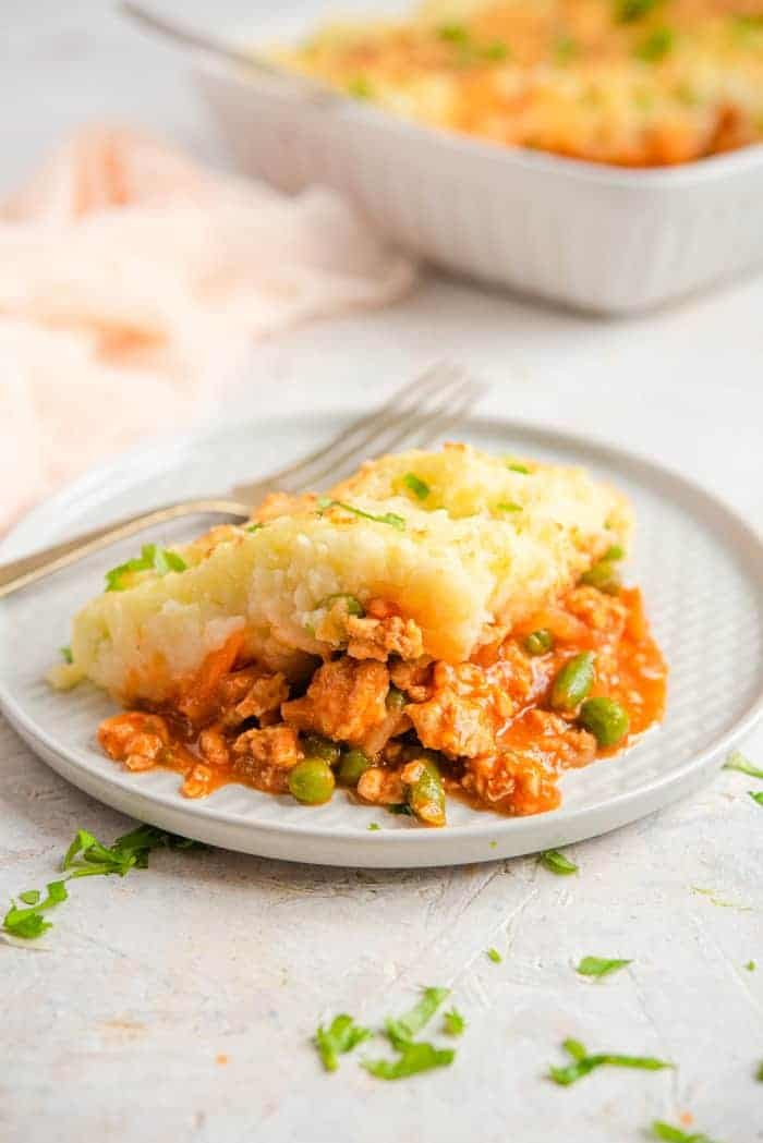 A slice of shepherds pie on a plate with a fork