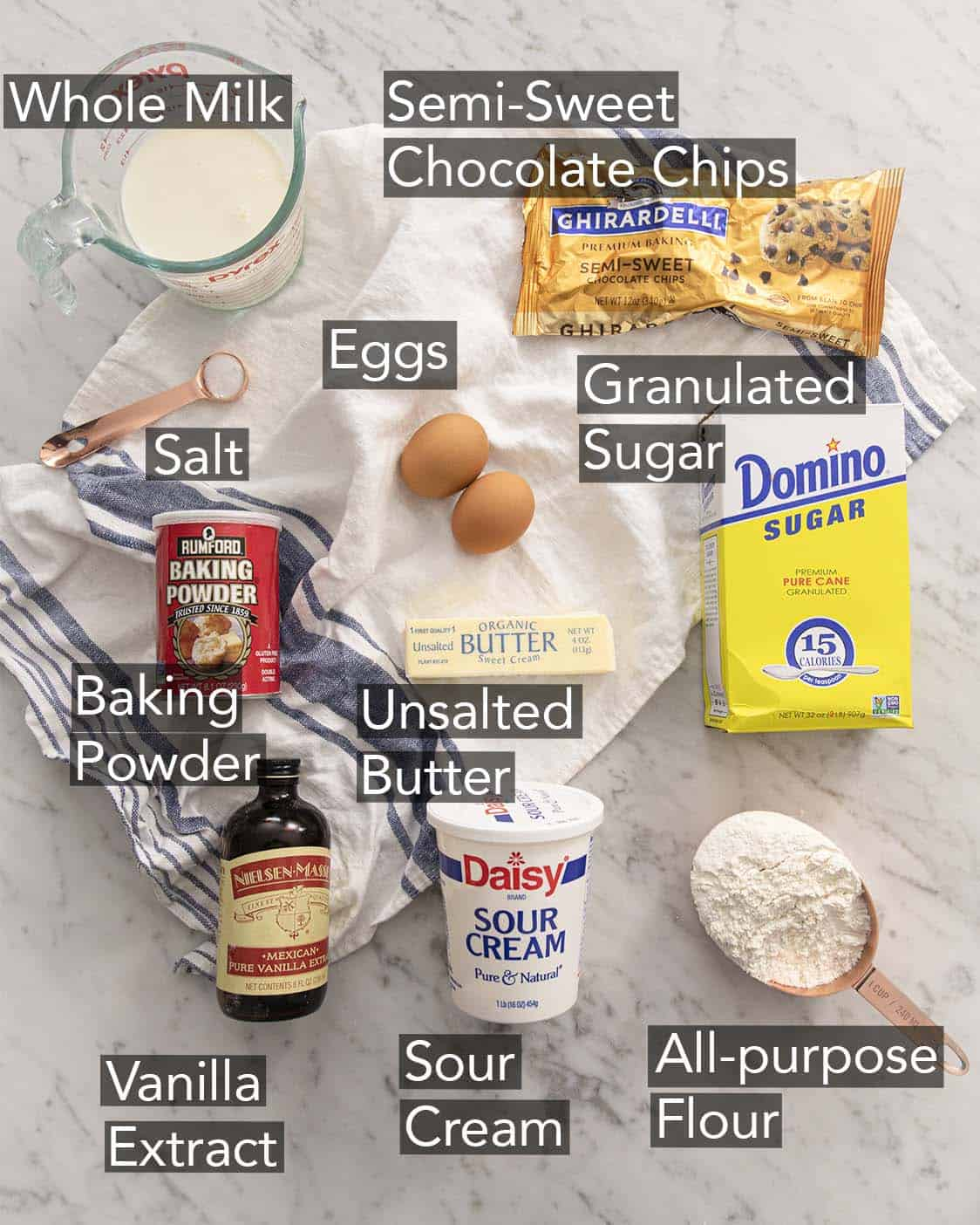 Ingredients to make chocolate chip muffins on a marble counter.
