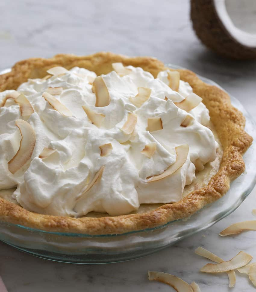 A Whole coocnut cream pie topped with whipped cream and toasted coconut.