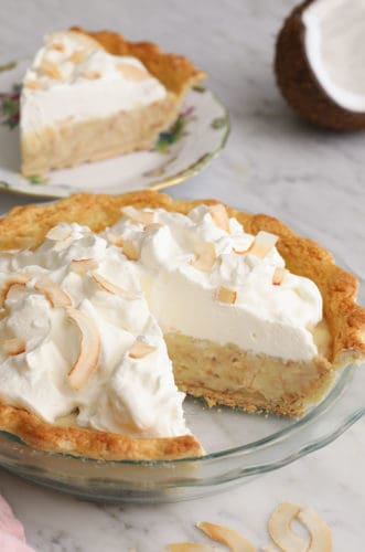 A coconut cream pie topped with whipped cream