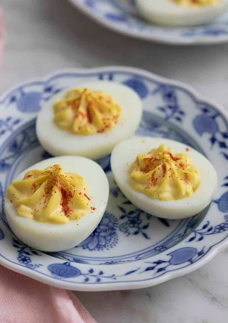 Three deviled eggs on a blue and white plate.