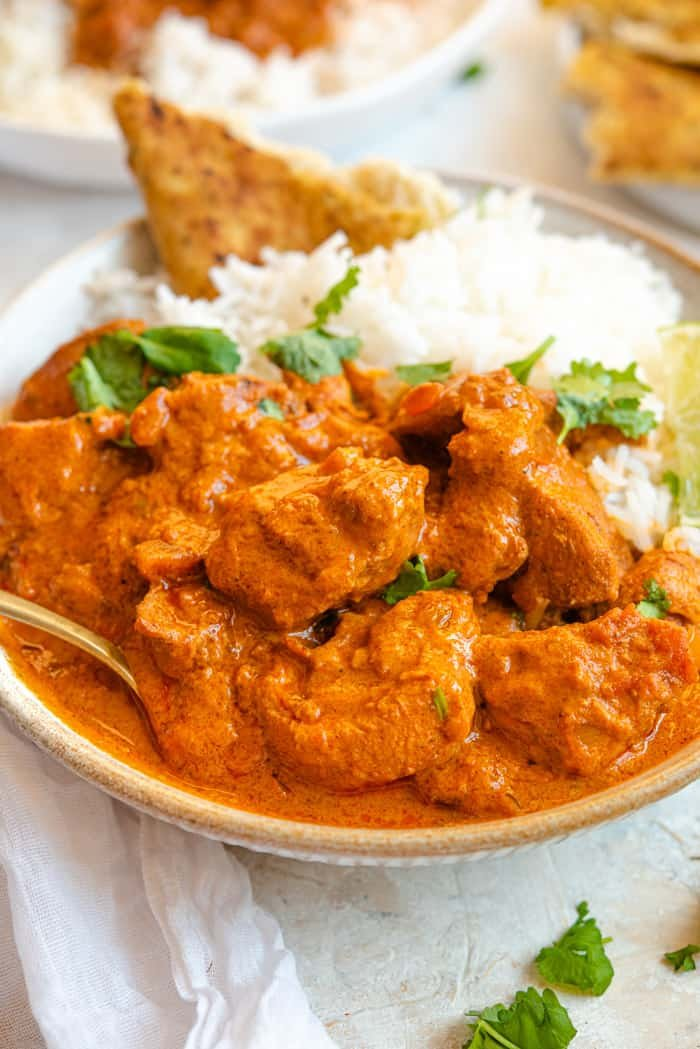 A close up of chicken tikka masala in a bowl with rice