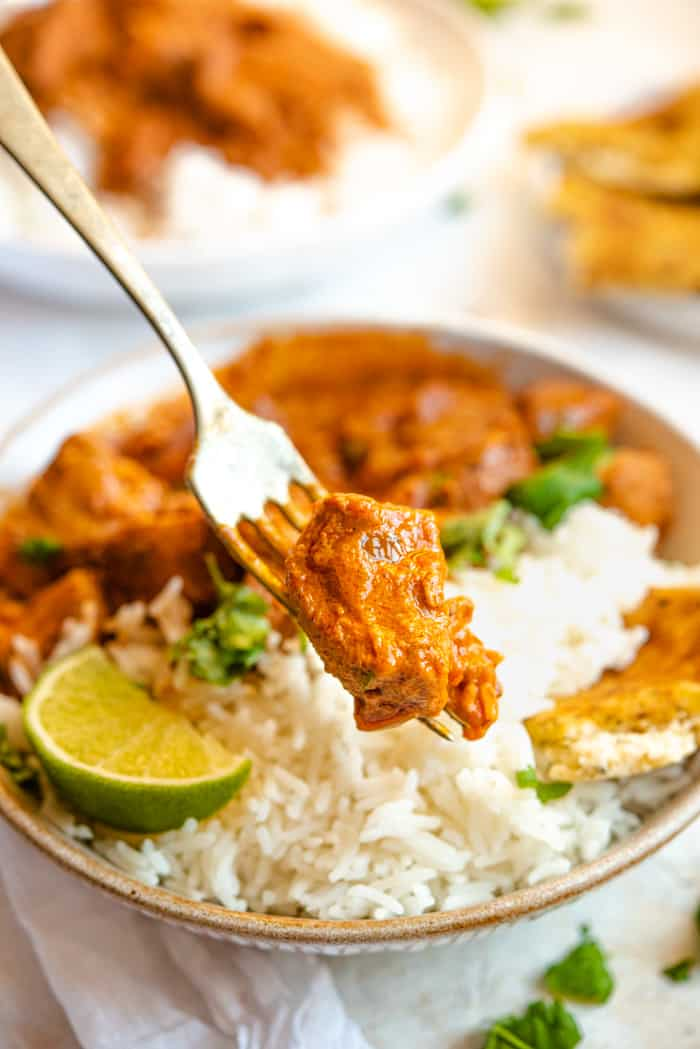 A close up of a piece of chicken curry on a fork