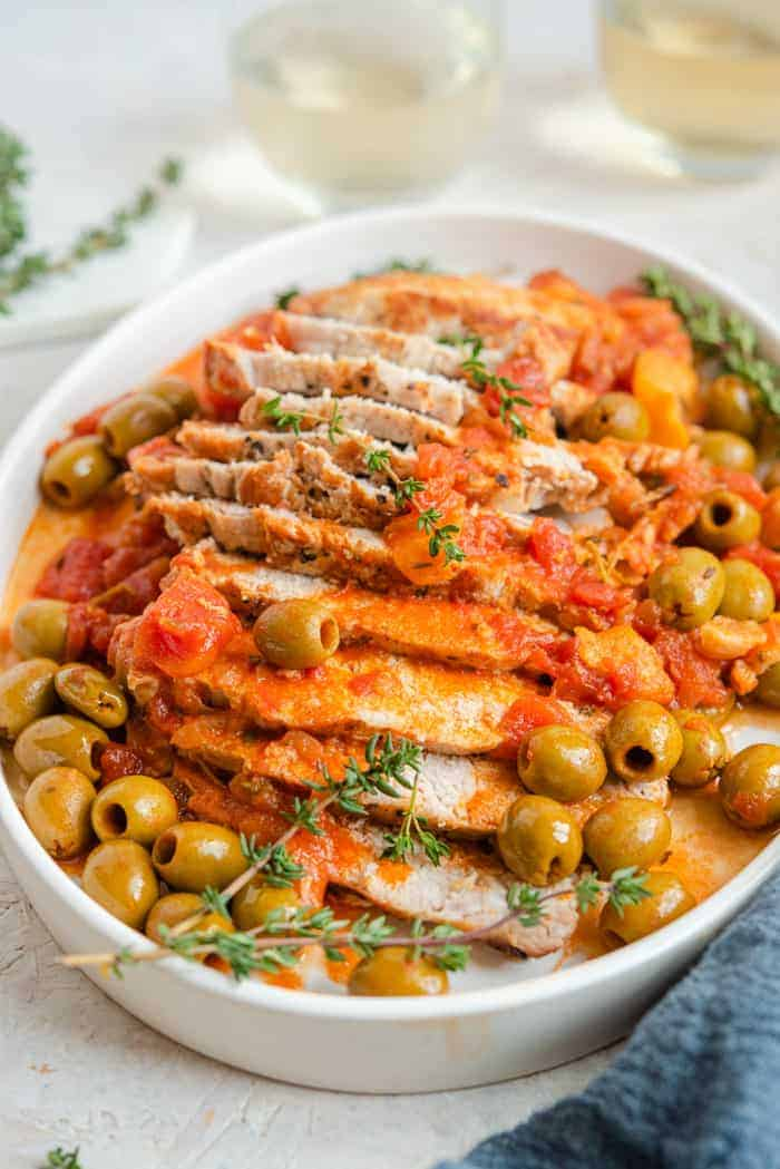 A close up of instant pot pork loin on a platter with olives and tomatoes