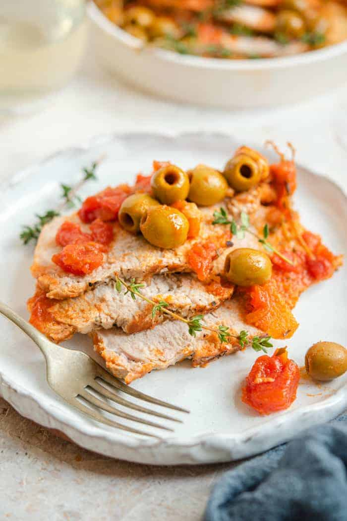 A few slices of pork loin on a plate with tomato sauce and olives