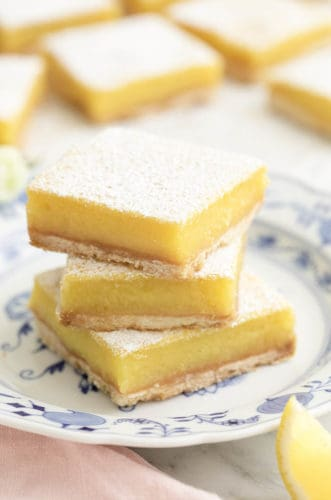 Three delicious lemon bars on a porcelain plate.