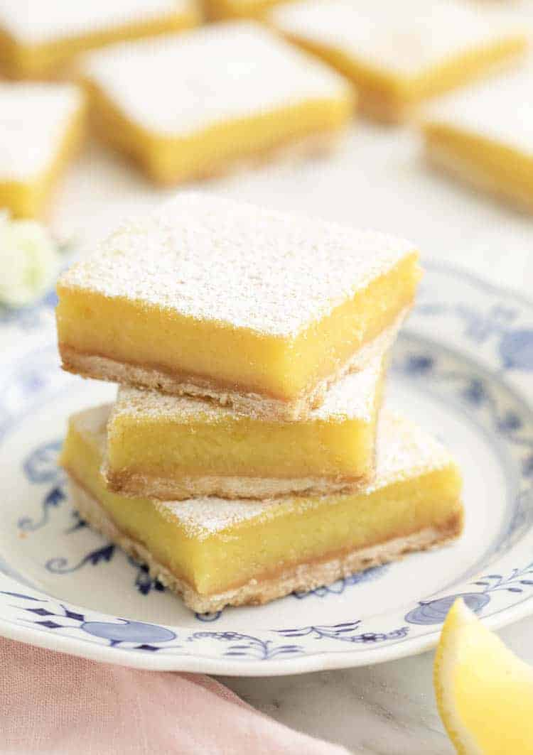 Three delicious lemon bars on a porcelain plate.