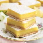 A stack of lemon bars on a porcelain plate next to a pink linen.