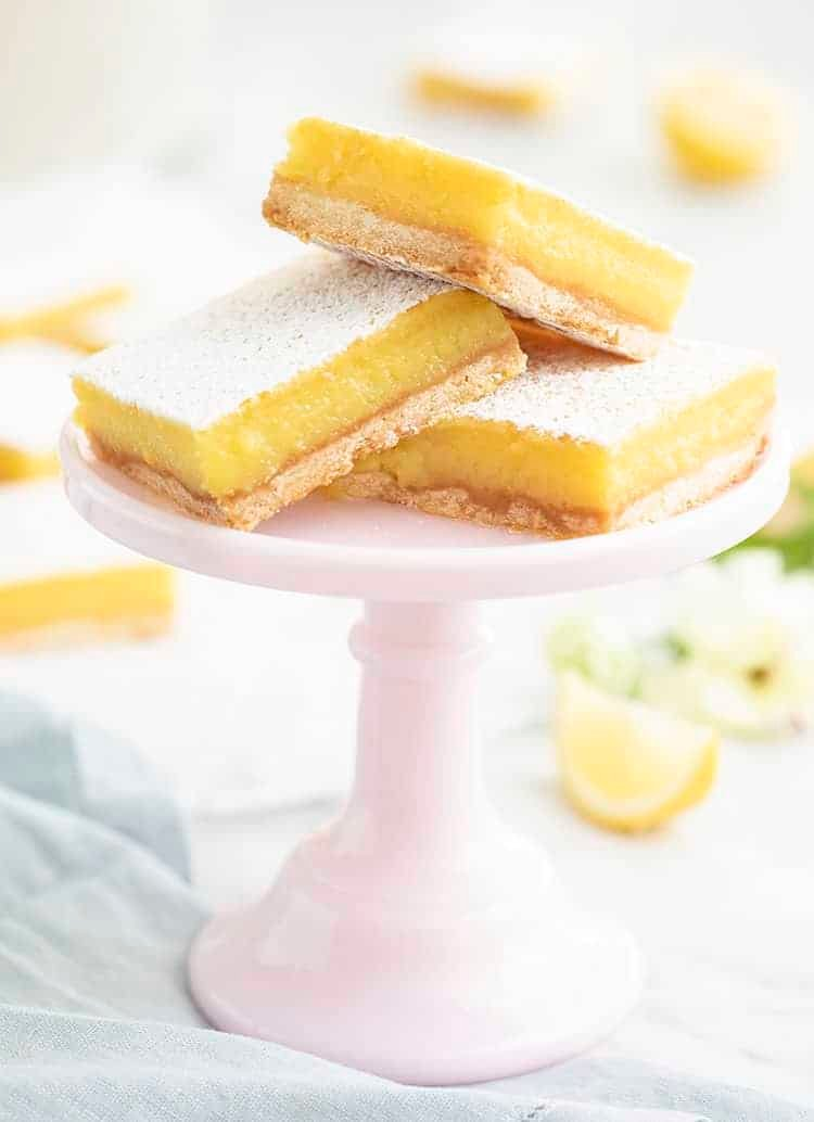 A group of lemon bars on a small pink cake stand.