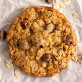 An oatmeal chocolate chip cookie next to some oats and chocolate chips on a piece of parchment paper.