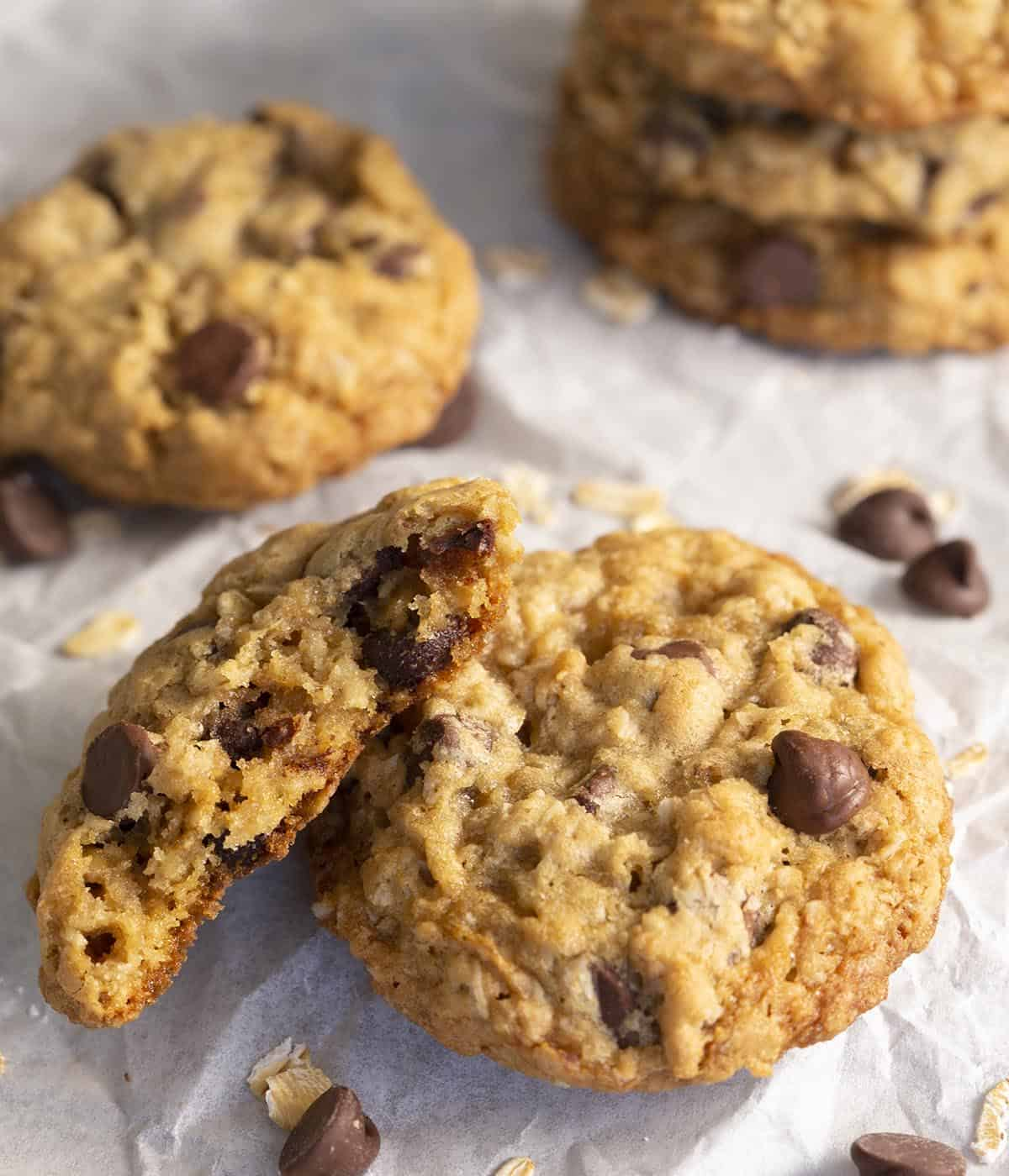 A group of Oatmeal Chocolate Chip cookies with on broken in half to show the chewy interior.