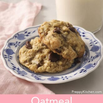 Two Oatmeal Chocolate Chip Cookies next to a glass of milk.