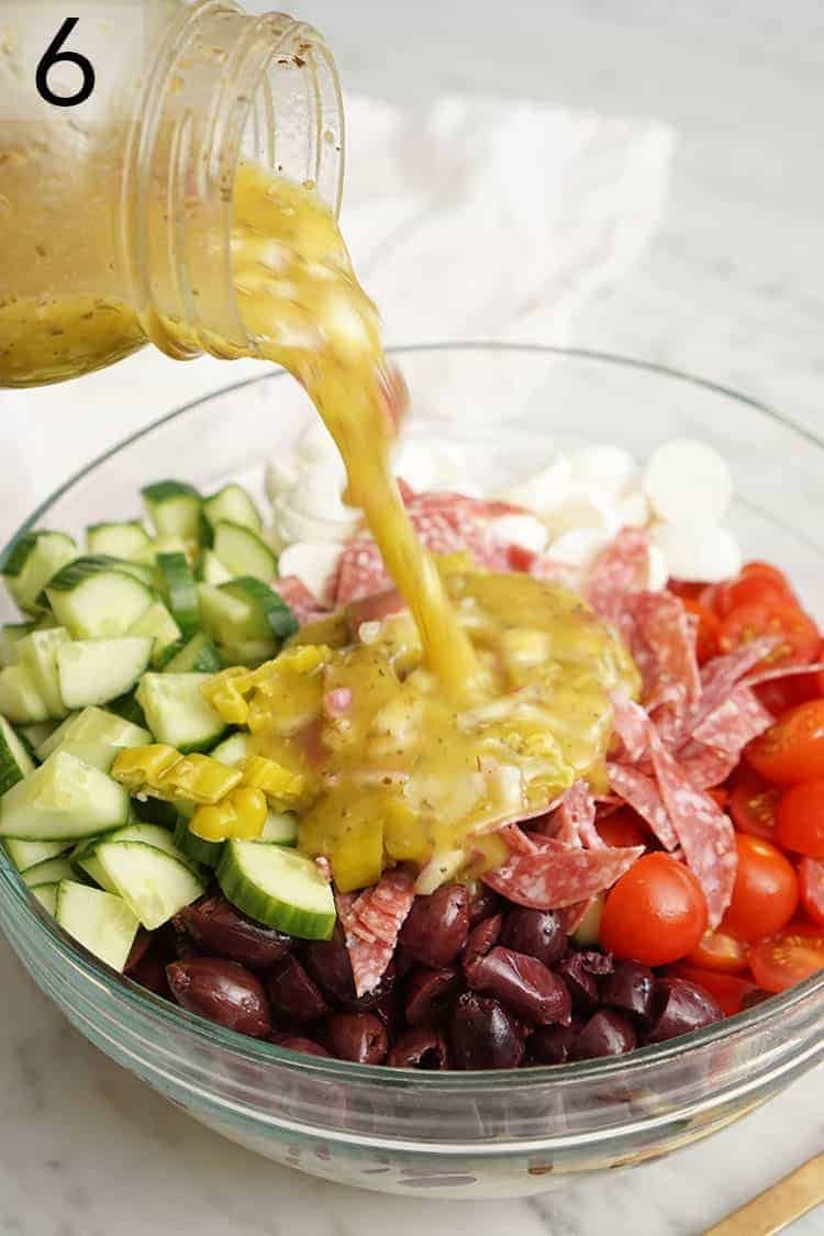 Homemade Italian dressing pouring onto pasta salad.