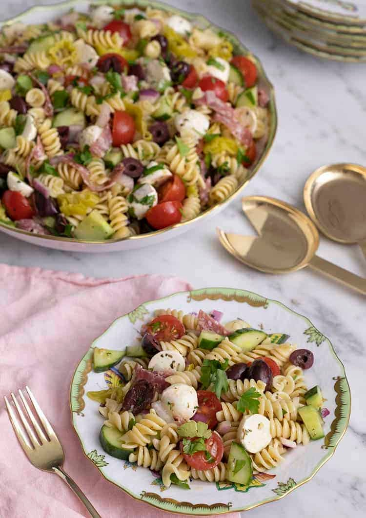 Pasta salad on a porcelain plate nest to a large serving dish.