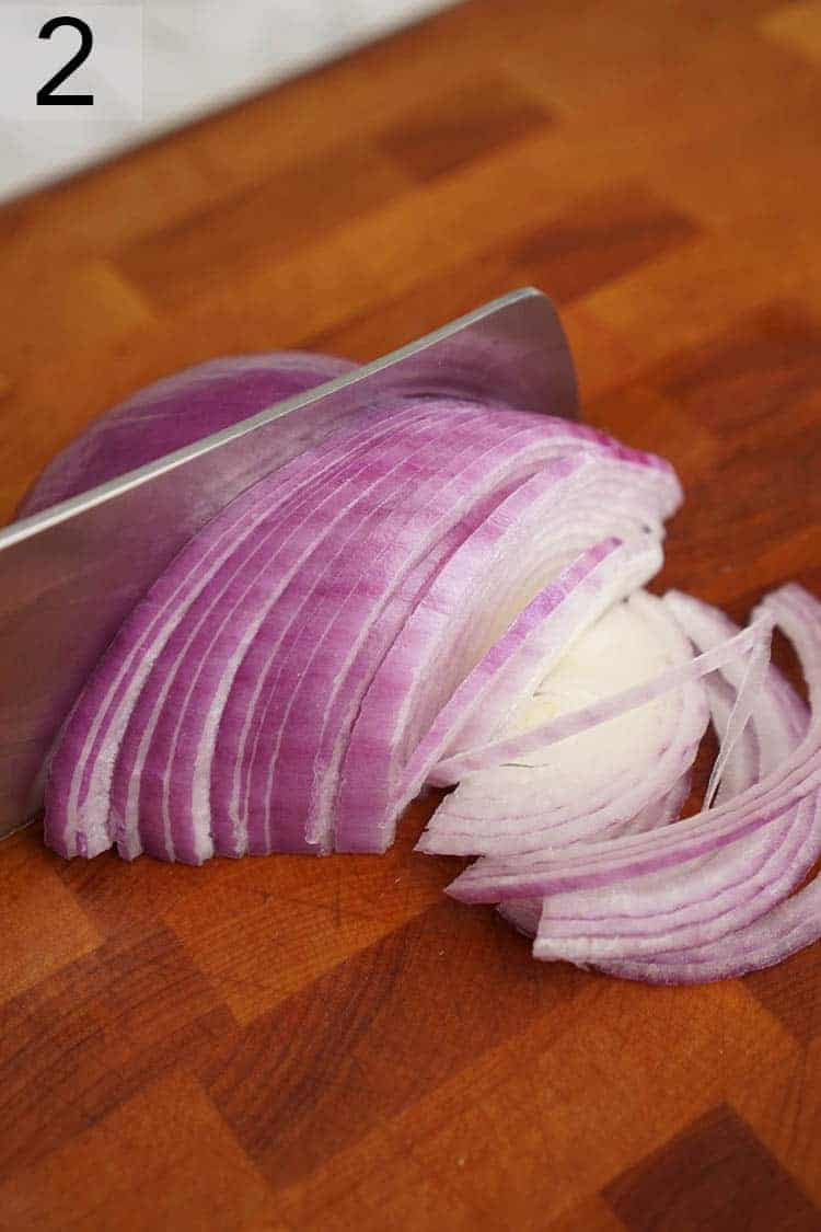 Red onions getting thinly sliced.