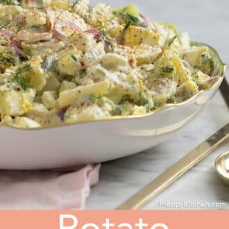 A potato salad next to golden serving utensils.