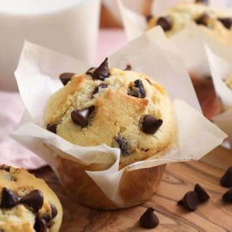 A chocolate chip muffin with a bite taken out next to a glass of milk.
