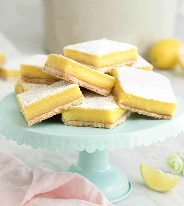 A large group of lemon bars on a blue cake stand.