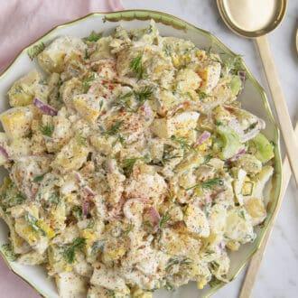 A potato salad on a porcelain serving plate.