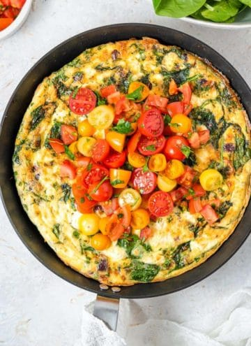 An overhead shot of a frittata topped with tomatoes in a skillet