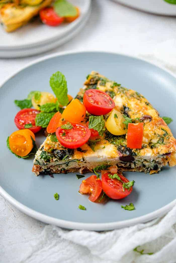 A slice of frittata on a plate topped with tomatoes