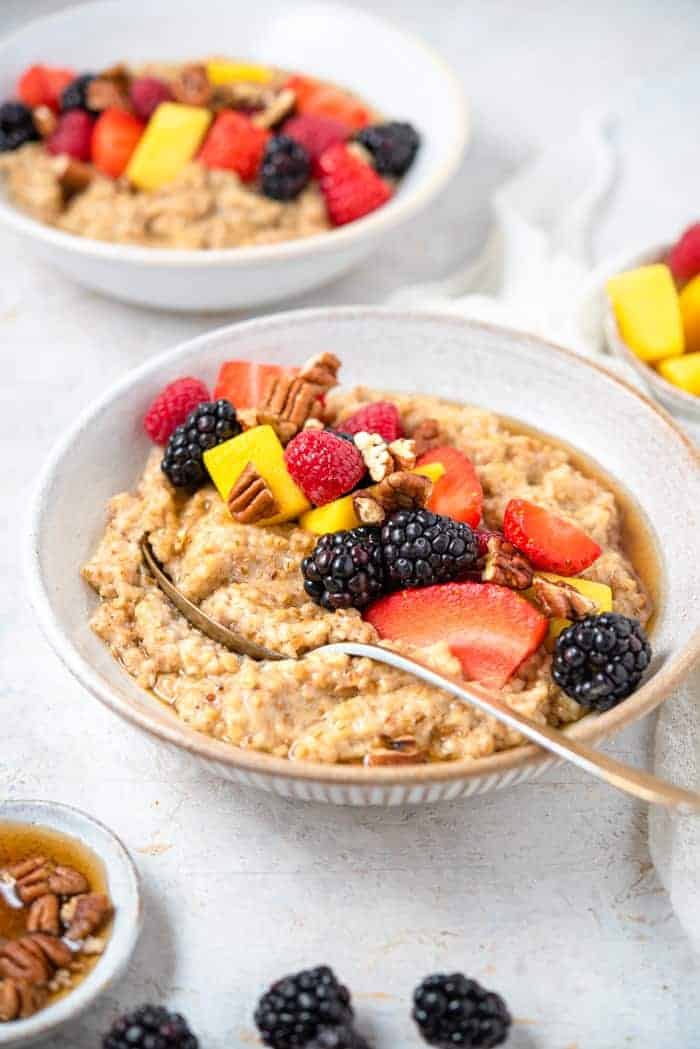 A side shot of cooked steel cut oats in a bowl topped with fruit