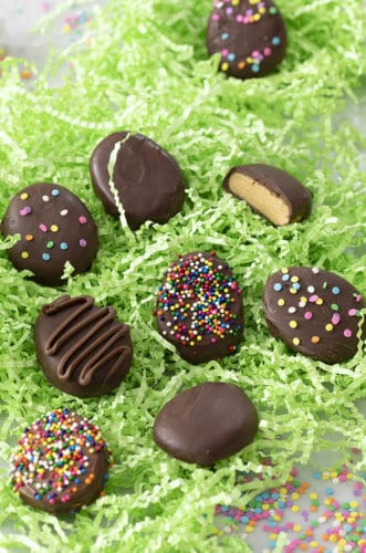Peanut butter eggs covered in chocolate in a bed of green paper grass.