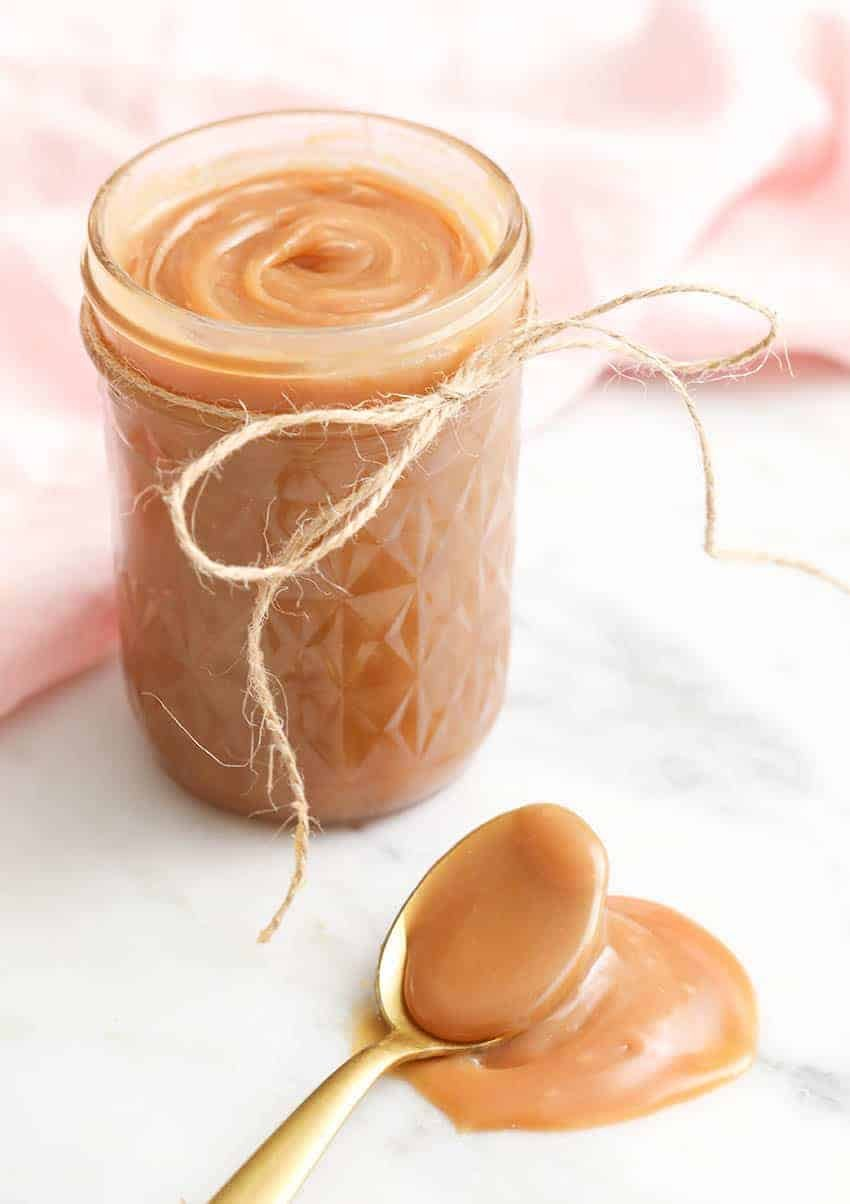 A jar of homemade caramel with a giolden spoon in the foreground.