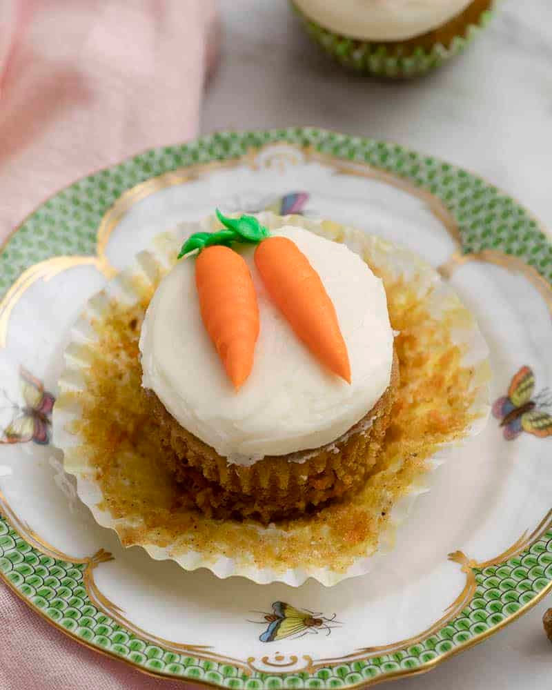 An unwrapped carrot cake cupcake topped with two buttercream carrots on a plate.