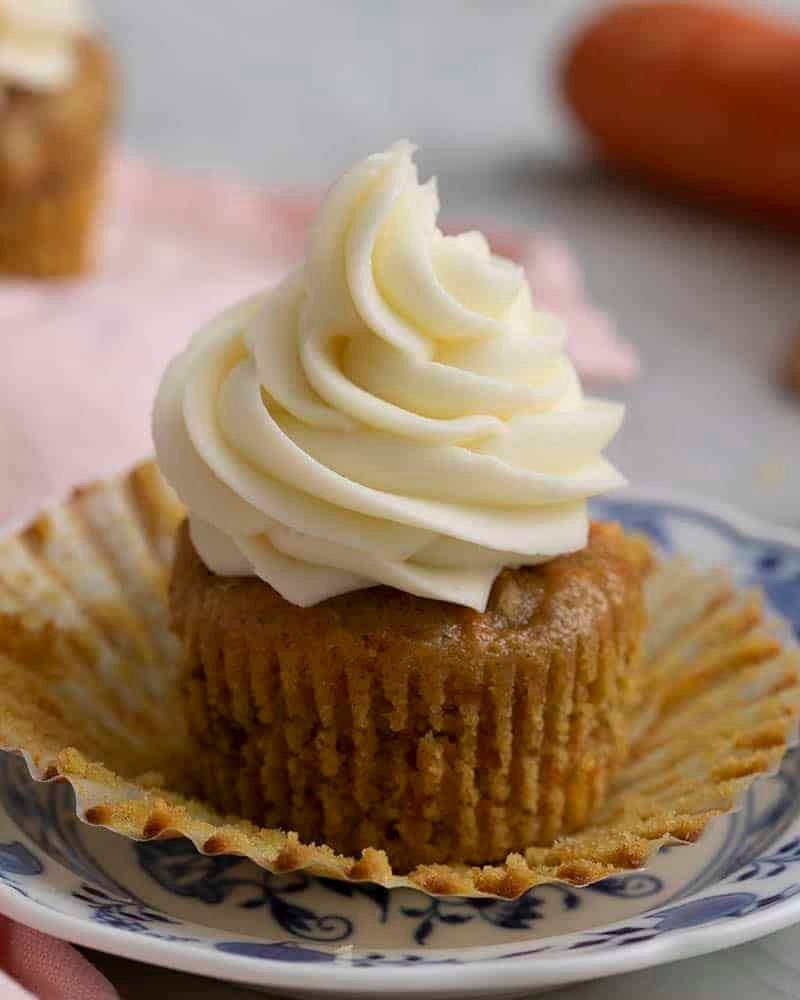 A carrot cake cupcake with the paper removed on a plate.