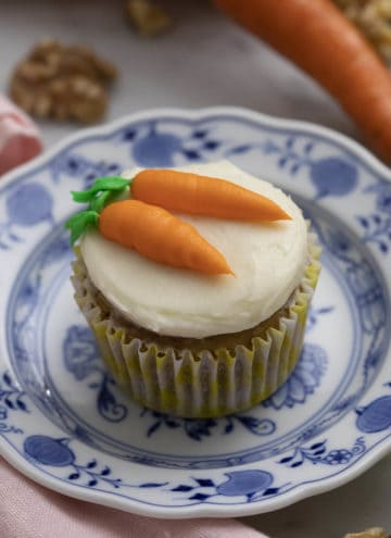 A carrot cake cupcake with two buttercream carrots piped on top.