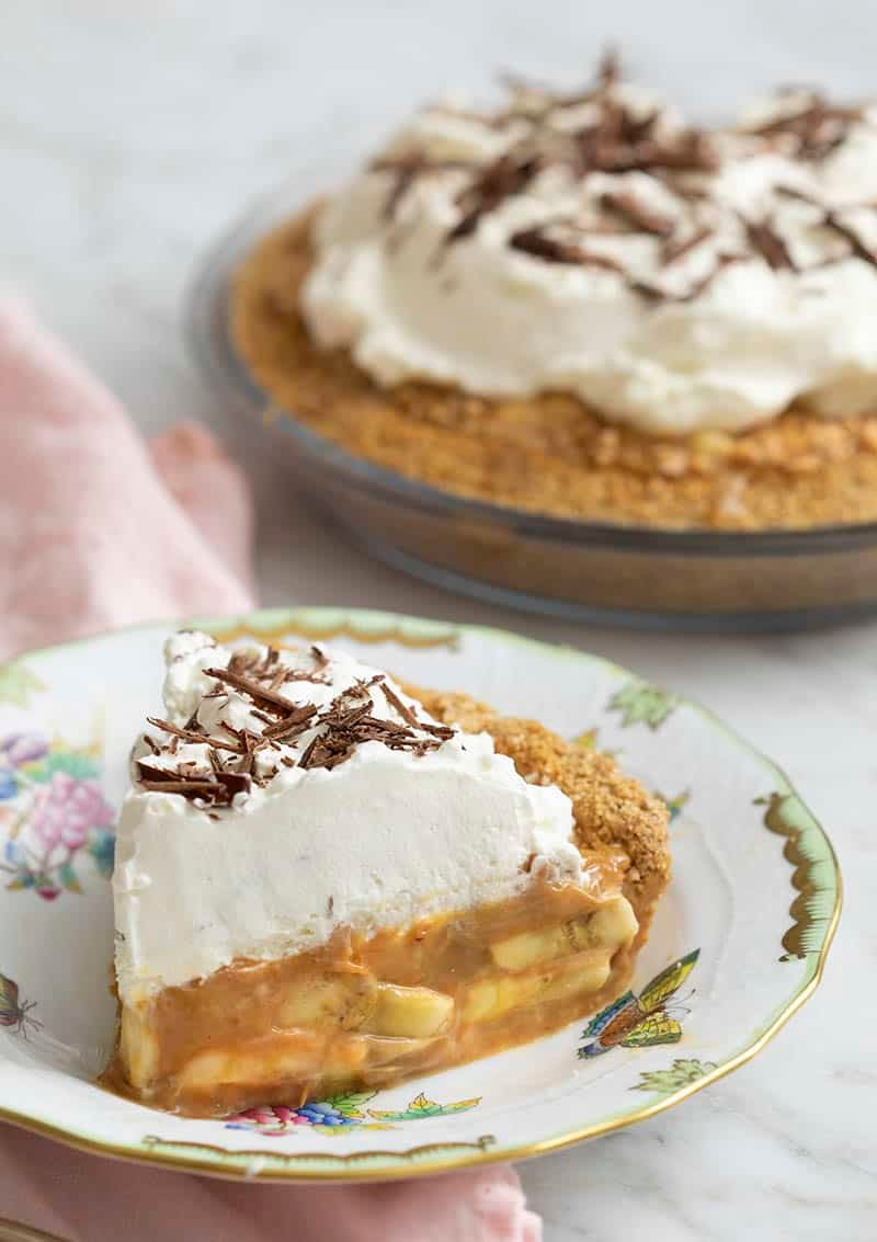 A piece of delicious banoffee pie in the foreground with the whole pie behind it.