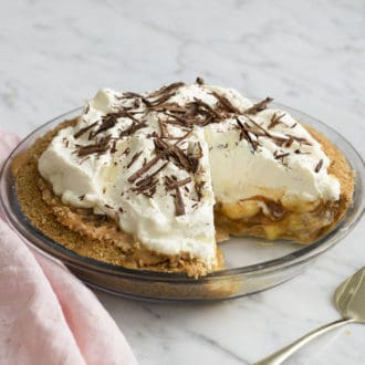 A banoffee pie topped with whipped cream and chocolate shavings in a glass pie dish.