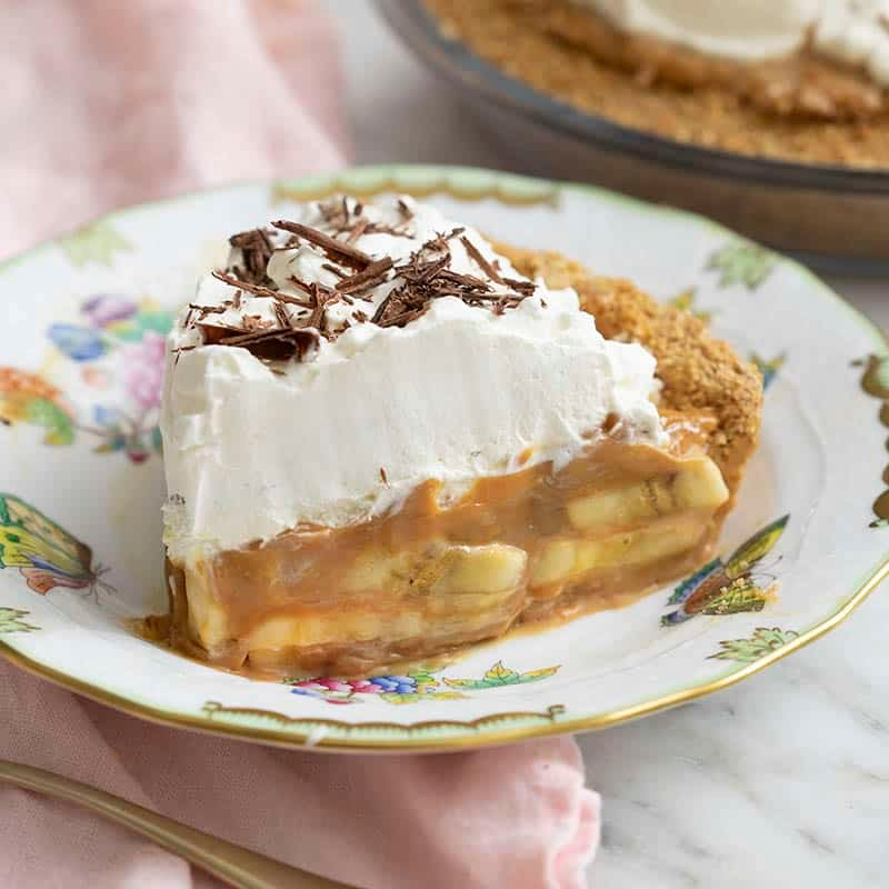 A piece of banoffee pie showing the bananas and dulce de leche inside.