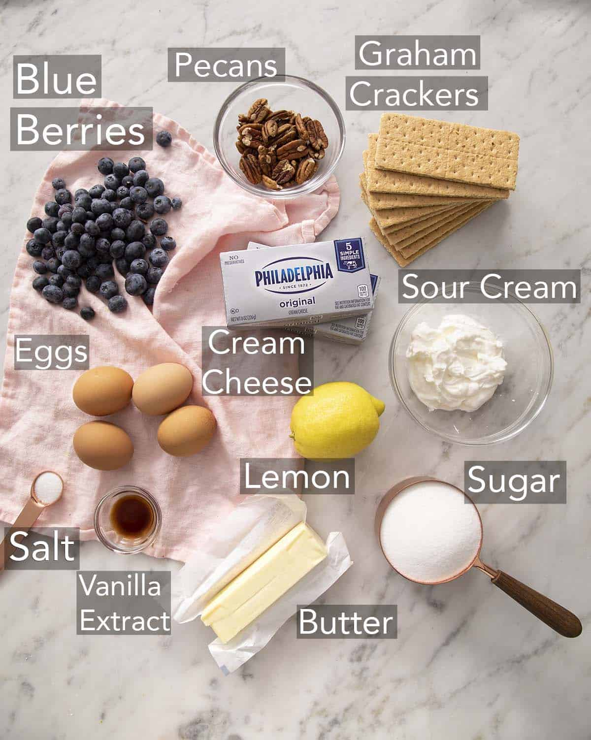 Ingredients for making blueberry mini cheesecakes on a counter.
