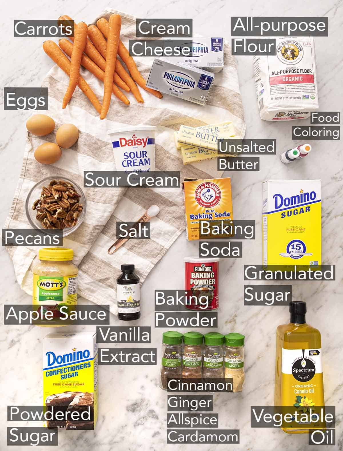Ingredients to make carrot cake on a marble counter.