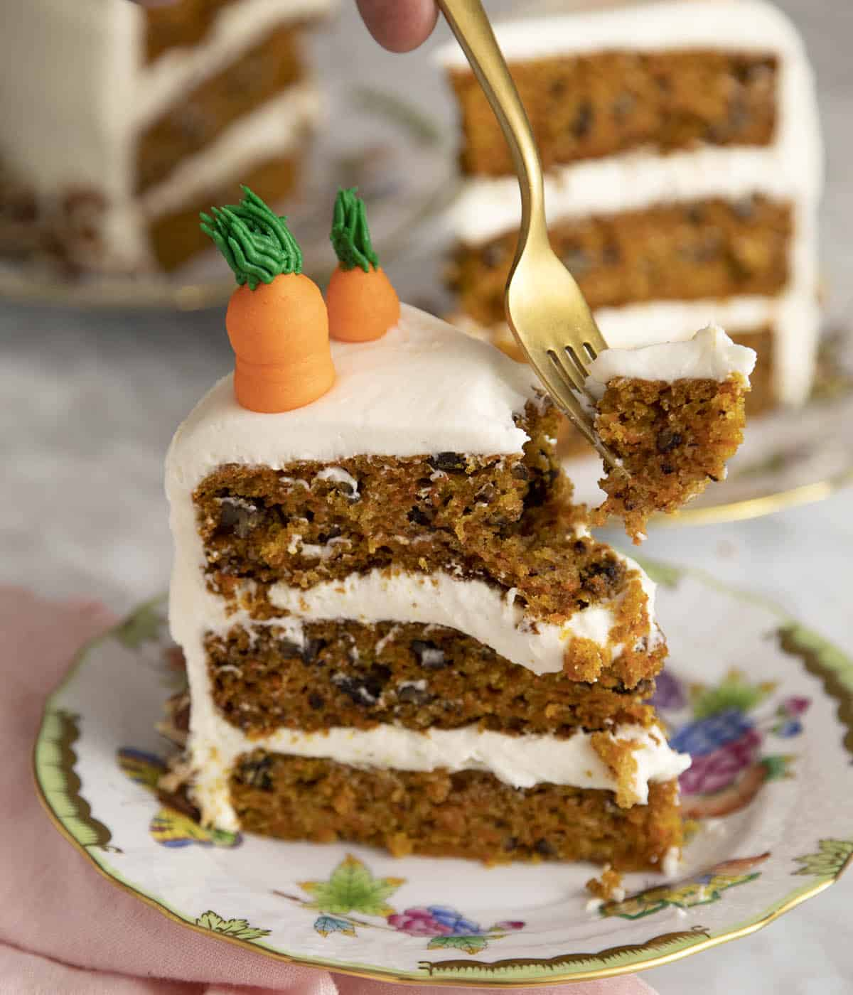 A piece of carrot cake being eaten with a golden fork.