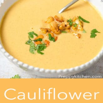 cauliflower soup in a white bowl with a spoon