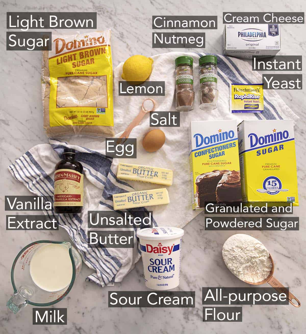 Ingredients to make cinnamon rolls on a marble counter.