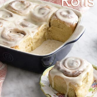 Cinnamon Rolls with glaze in a square baking dish with one in the foreground on a plate.