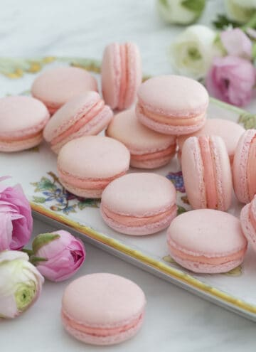 A group of pink macarons on a serving tray next to flowers