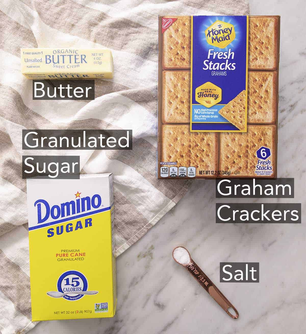 Ingredients to make a Graham cracker crust on a marble counter.