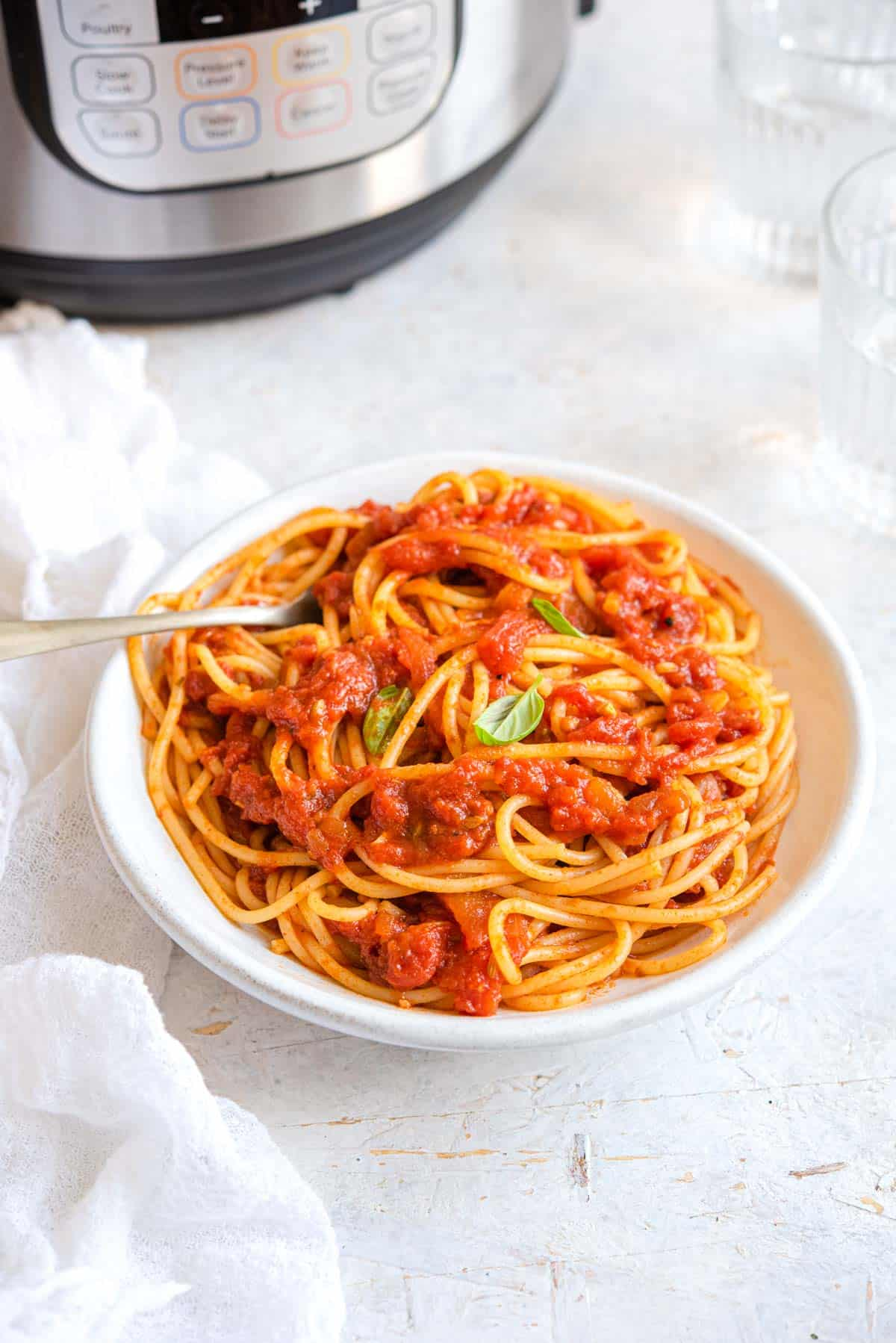 Spaghetti with tomato sauce in a bowl with an Instant Pot in the background