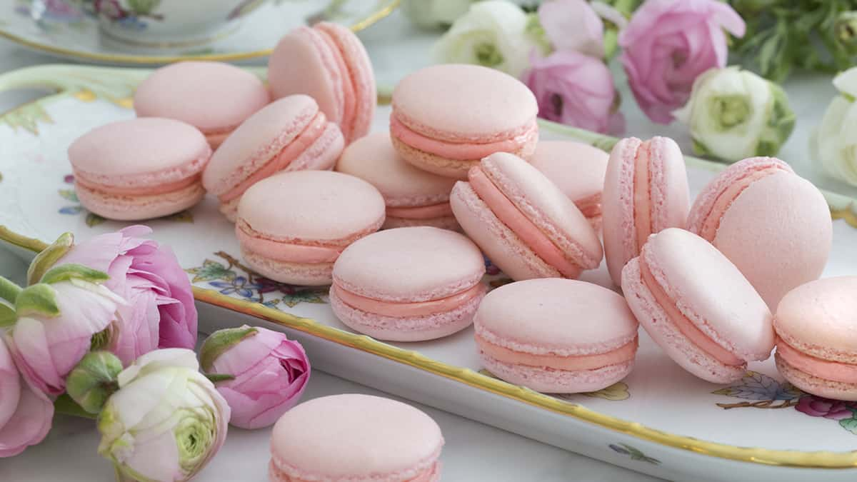 A group of beautiful macarons on a serving tray next to flowers.